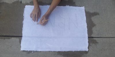 A digital photograph taken above of a white sheet of paper onto a sidewalk. The camera angle is pointing down, and the paper is in the center of the photograph. Wet marks from the paper sink into the cement, creating a darker, water stain. Two hands with a yellow pencil are extending out of the top center of the frame, writing on the white sheet of paper material.