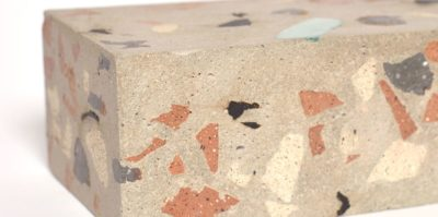 A digital photograph of a corner of a brick sculpture. This photo, taken very close to the sculpture, has a small amount of white background space in the top left corner. On the brick sculpture, marks in earth tones of brown, orange, beige, and black are painted in small, and are painted in various shapes and sizes.