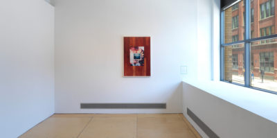 An installation photograph of a framed photograph centered on the gallery wall. The right wall has two windows, letting in natural light. The photograph is framed in a thin, white frame. The photograph begins with an image of dark wood as a border. Centered inside is another photograph of a framed image of the ocean. Behind the ocean image is a photograph of a burning bridge.
