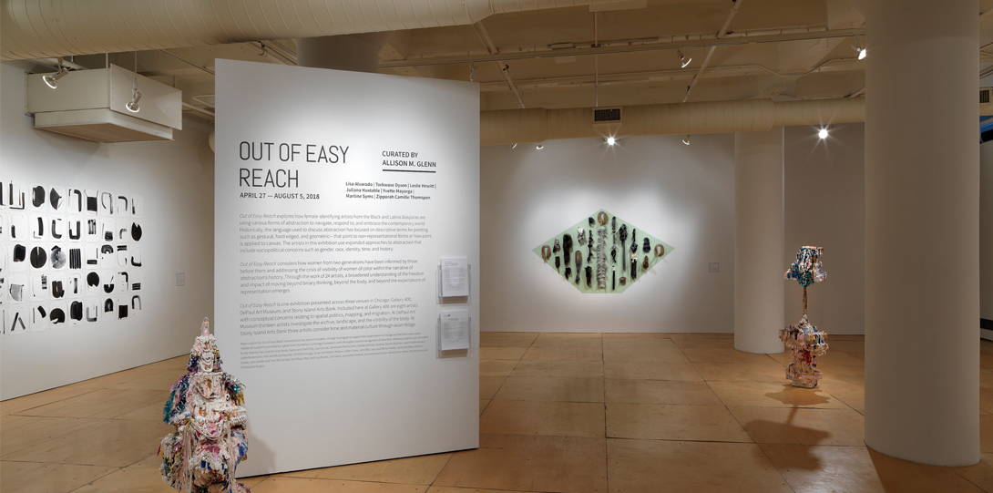 """An Installation photograph of the gallery. A separate, square column stands on its own in the center of the photograph. On the column is adhered text of the exhibition information. The title, in large, bold texts, writes, """"Out of Easy Reach"""". On another wall to its left is a large black and white print of multiple different shapes. On another wall to its right is a pained, large, green rhombus. Adhered to the rhombus are various types of hair yarn, and materials."""