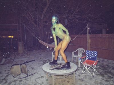 A photograph of a middle-aged person standing on a table in a backyard. The setting of the photograph is at night, while it is snowing. The middle-aged person is painted in full body paint. From their head to their feet, the body paint is in a gradient of blue, green, and orange. The person is wearing a gold necklace and black leather boots. Behind them, are plastic chairs, a fence, a hammock and a picnic chair. The picnic chair's print material is the american flag symbol.