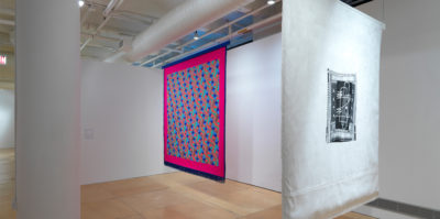 An Installation photograph of two large, ceiling to floor length, square textiles. The textile on the left has a thin, dark blue border with fringe draped from the bottom. Inside this border is another, much thicker, dark pink border. Inside is a zig-zag design of small squares in blue, red, teal, and orange colors. The textile on the right has a thick, white border. Inside the border is a smaller, black rectangular shape with white drawings of lines,dots, dashes and bolded lines.