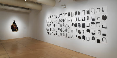 An installation photograph of the side walls of the gallery. On the right wall, four long rows of black shapes are painted on square papers. The four rows of paper extend horizontally across the entire wall. On the left wall is a three-dimensional sculpture made of brown yarn and other dark, found materials. The three-dimensional sculpture is in the shape of an upside-down heart