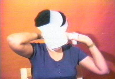 A film still of a middle aged person. The film still is of the person's front profile from the shoulders up. Behind the person, is an orange wall. The person is in the motion of wrapping a white cloth around their face.