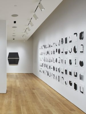 An installation photograph of the side walls of the gallery. On the right wall, four long rows of black shapes are painted on square papers. The four rows of paper extend horizontally across the entire wall. On the center wall to its left, there is a large, black sculpture of two trapezoids adhered to the wall.