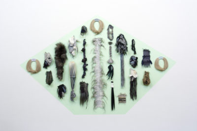 An installation photograph of multiple found materials of materials. Materials include textiles, hair and yarn. All materials adhered to a green painted background.