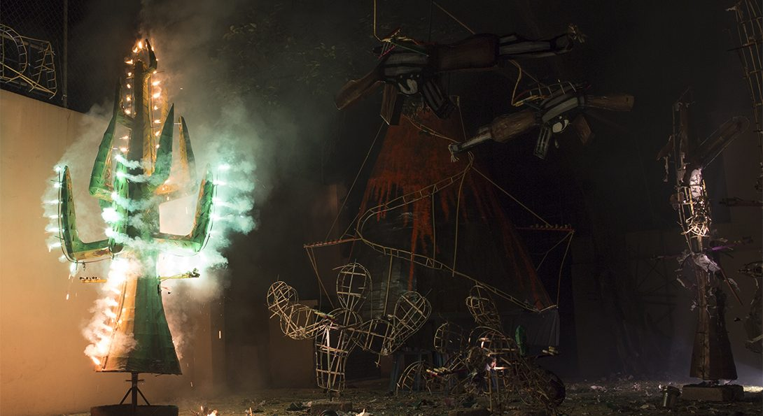 A photograph of a pyrotechnic performance at night-time. .A green tree sculpture is burning with a green glow. Behind the green- glowing sculpture is multiple, unlit, metal sculpture outlines.