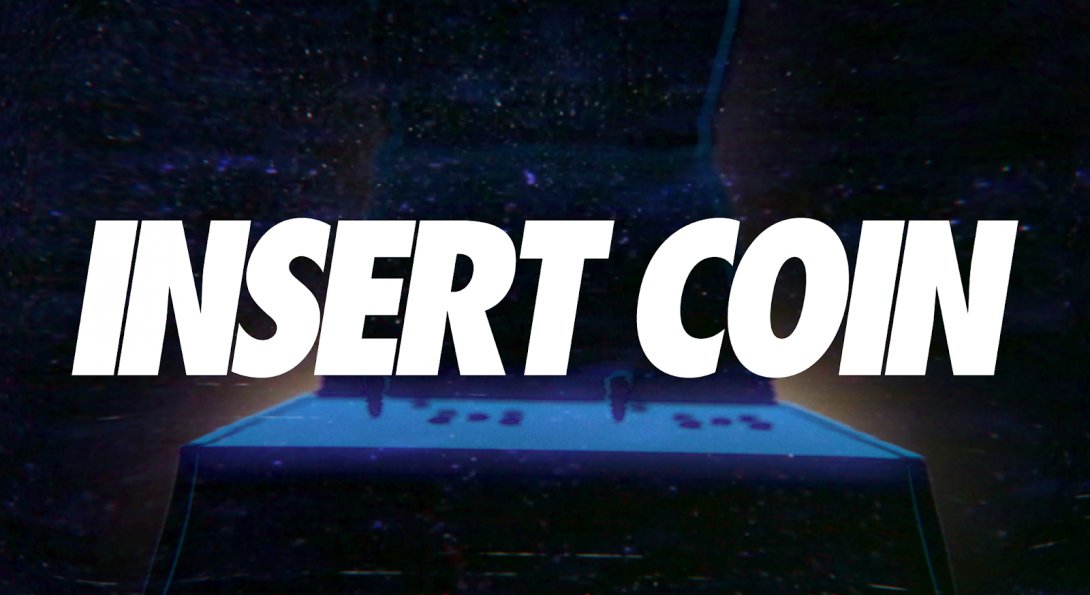 """A created image with the words """"Insert Coin"""" in bold, white, large letters. Behind the text is a dark blue image of a game machine and a dark blue background."""