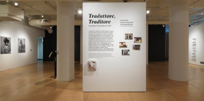 """An Installation photograph of the gallery. A separate, square column stands on its own in the center of the photograph. On the column is adhered text of the exhibition information. The title, in large, bold texts, writes, """"Traduttore, Traditore"""". On the left wall, there are two large black and white, portrait photographs of middle-aged people."""