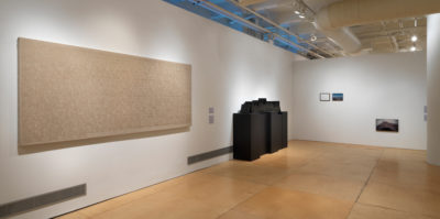 An installation photograph of two gallery walls meeting in a corner. On the left wall, there is a large, tan canvas. The canvas is about nine feet wide and 3 feet tall. To the right of the vancas is a large, four foot tall sculpture made of wood, painted entirely black. The sculture's base is four large rectangles. On the right wall there are two images, eight by ten inches small. The pair of images are about two inches apart from each other. The image on the left is a mostly-white space in a black frame. The image, closely on the right, is of a landscape with a blue sky.