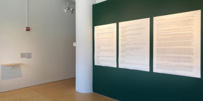 An installation photograph of two gallery walls. The wall on the left is white and the wall on the right is a dark green color. The wall on the left has a wooden shelf installed, with a small translucent paper placed on top. The dark, green wall on the right has three, large, archival pigment prints. The prints are arranged in the center of the wall in a horizontal line. Each print is about three feet tall and two feet wide. The color of the prints are white with small black text.