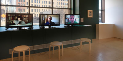 An installation photograph of three, small, computer monitors. The computer monitors are situated on a dark green painted wall's window edge. The monitor on the left is a still of a middle-aged person, seated at a desk, talking. The center monitor is a still of a middle-aged person from the chest up, looking at the camera. The monitor on the right is of an older-aged person from the shoulders up, looking at the camera.