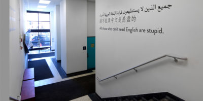 """An installation photograph of the entrance outside of the gallery. The left side of the photograph is of stairs leading down to the ground floor. Ahead of the stairs is a hallway with black rugs leading to a ceiling to floor length window. On the right wall of the stairs, the sentence """"All those who can't read English are stupid."""" is printed horizontally on the wall. The sentence is written in three different languages."""