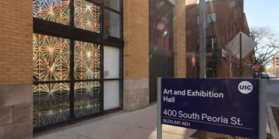 """A photograph of the outside of a building. The building has two sets of three large windows between light-brown brick walls. Printed and displayed from the entire building window is a gold design of kaleidoscopic triangles. On the right side of the photograph, a blue sign reads """"Art and Exhibition Hall, 400 South Peoria Street"""""""