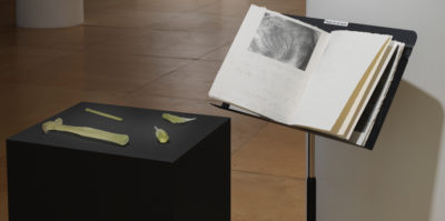 An installation photograph in the gallery space. On the left, a three foot tall, square podium is painted black. Placed on the podium are four sculptures made of sugar. The sculptures include replications of a hammer, a screwdriver, a pencil, and measuring tool. To the right of the podium piece is a black music sheet stand. An open book with a black and white photograph is placed on the stand.