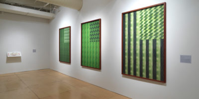 An installation photograph of two gallery walls. On the wall to the left, there is a shelf installation. On the shelf is an open book with red binding and white pages. The wall on the right side has three large, mounted, wooden-framed, ink-jet prints. The ink-jet prints are about the size of a standard american flag. Each print is a replication of the american flag, printed in variations of green shades.