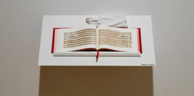 A photograph of an open book on a white shelf. The book has red binding and white pages. Printed on the pages are musical note sheets in black ink. A white glove sits on the end of the shelf.