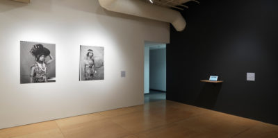 An installation photograph of two walls in the gallery. The left wall is painted white. Mounted on the left wall are two black and white, portrait photographs of middle-aged people. The size of the portraits are about three by two feet large. The right wall is painted black. Installed on the black wall is a white, thin shelf. Situated on the shelf is an iPad.