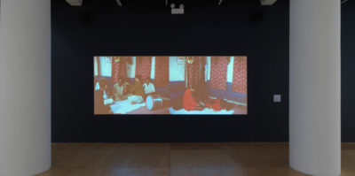 An installation photograph of a film room. Situated in the film room is a large projected film, paused on a film still. The film still captures two side-by-side scenes. The scene on the left is a group of five people sitting in a circle on the floor with a drum instrument. The scene on the right is one person sitting on the floor. Both scenes are in the same location of a room with red curtains.