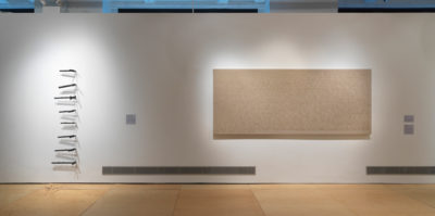 An installation photograph of a white gallery wall. On the left side of the wall, eight three-dimensional, thin objects are adhered in a vertical line. On the right side of the wall, there is a large, tan canvas. The canvas is about nine feet wide and 3 feet tall.