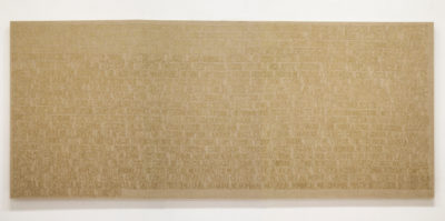 A photograph of a large canvas that is 9 feet wise and three feet tall. The canvas is a light brown color. In hand-written text, a paragraph in spanish language covers the entirety of the canvas. The hand-writing is written in a dark, tan color.