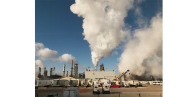 A landscape photograph is taken outside a Citco factory. The landscape of the factory, machinery, cars and containers extends across the lower portion of the photograph. In the middle of the photograph, a big white smoke cloud is coming out of one of the pillars in the factory. It is blended with the clouds on the upper left part of the image. Taking up the entire right side of the landscape is dark gray smoke, covering up the blue sky behind it. There is a red car at the right bottom part of the image.