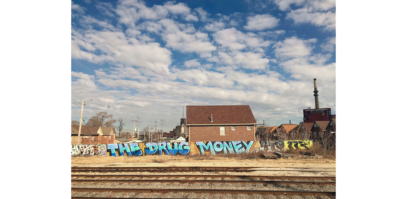 """A digital photograph that documents a landscape structure beside three sets of train tracks. The wall of the structure is covered in an assortment of graffiti. In the center of the wall, the largest piece of the graffiti is blue text that reads, """"The Drug Money"""". Peeking behind the graffiti wall is multiple, identical, one-story, brown homes, accompanied with electric poles that stretch into the far distance of the photograph."""