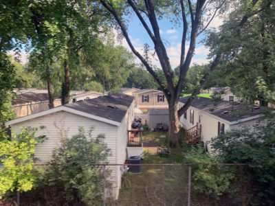 A digital photograph taken behind a metal fence of a backyard of two mobile homes.. The setting is photographed from an elevated point of perspective during a sunny midafternoon. Two sides of the houses are facing each other with a small yard in between them. The shared yard is in the center of the photograph. Three full grown trees with green leaves are planted on the left, center and right side of the houses. Emerging between the tree branches is a clear blue sky with few clouds. The center tree is the largest, extending from the center of the photograph to the top right, center, and left sides, creating a vignette with its leaves and shadow. Beside the trunk of the tree, and the center space of the mobile homes, sits an assortment of bicycles, wooden stairs and a plastic bag.