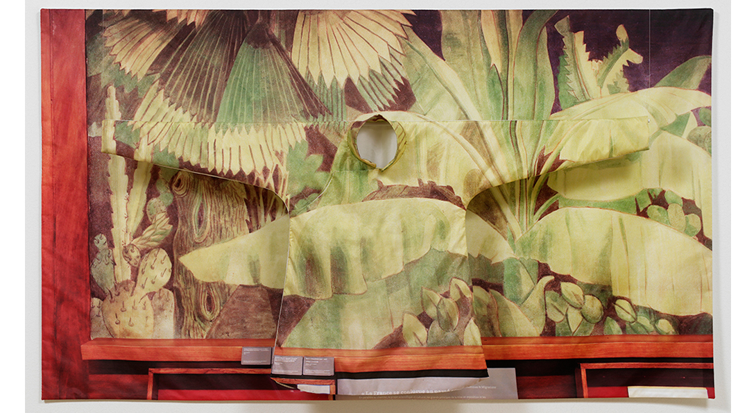 A photograph of a textile against a thick wooden frame. The textile is a drawing of various green plants. Placed over top of the textile is a long sleeve garment in the same pattern.