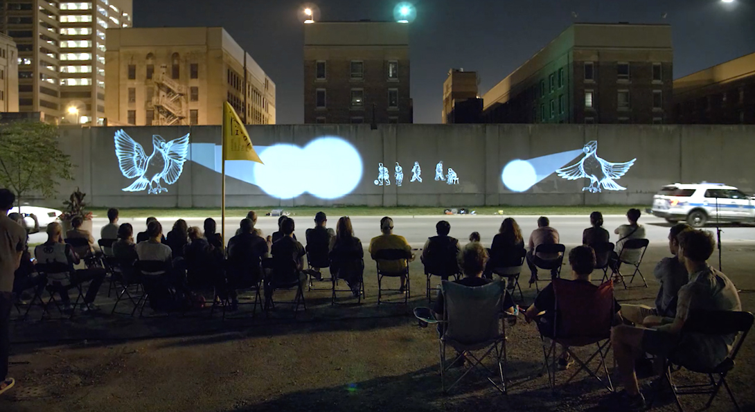 A photograph taken in the evening of about 28 people. They are sitting in lawn chairs, watching a projection against a concrete wall on the side of a highway.