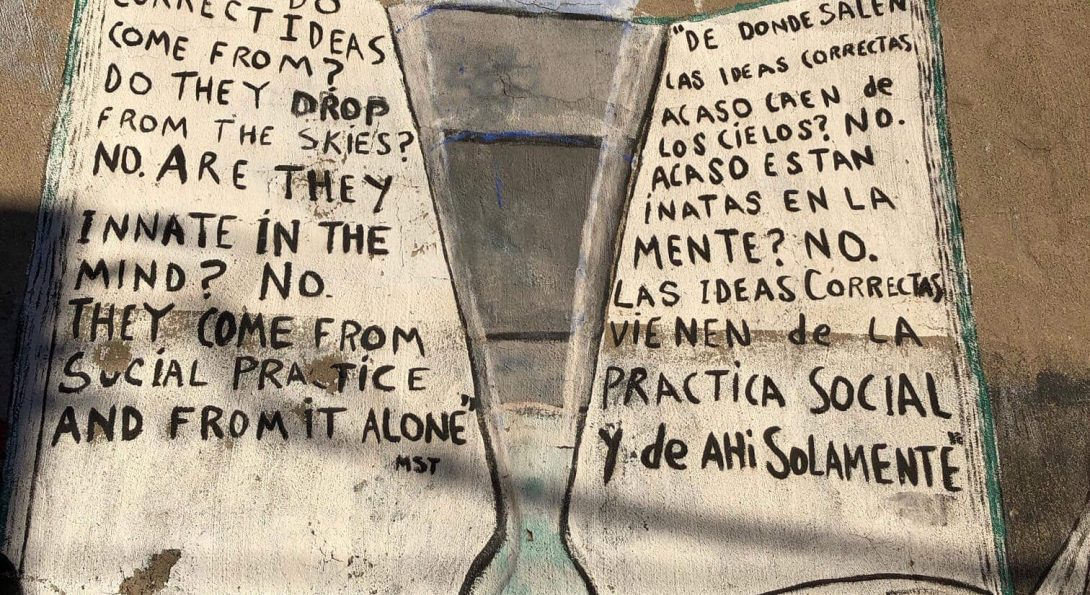 """A painting of an open book has an upside down triangular object in the middle. Text written in English and Spanish include sentences such as """"Where do correct ideas come from?"""" amd """"De donde salen las ideas correctas acaso caen de los cielos?"""