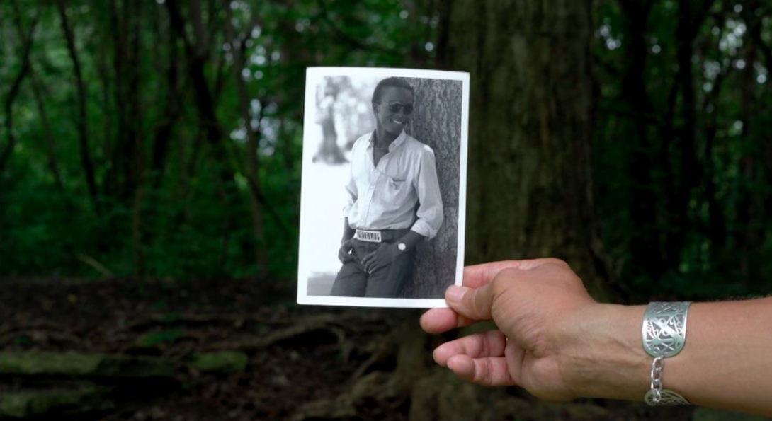 A photograph of a hand holding a black and white polaroid photograph. In the polaroid, there is a middle aged person standing beside a tree. In the background of the image, there is green trees.