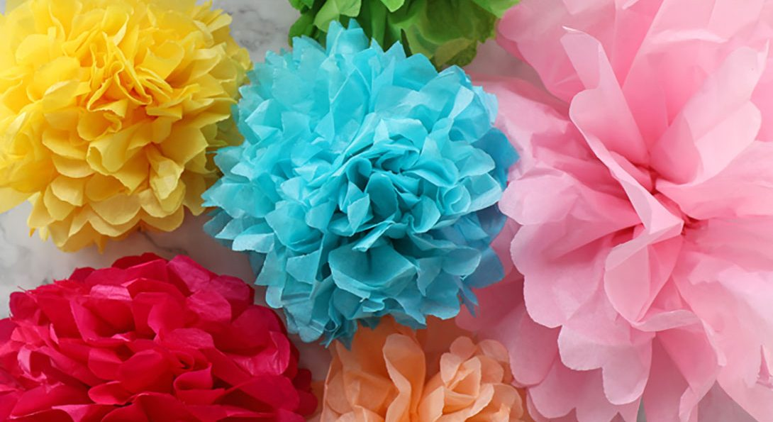 A photograph of six, colored tissues crafted into flower designs. Their colors are yellow, blue, pink red, orange, and green.