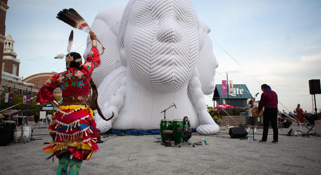 A large white sculpture of three heads, the size of houses, is placed in a courtyard. A young person is dancing in front of the sculpture. Next to the sculpture is a person playing an instrument.