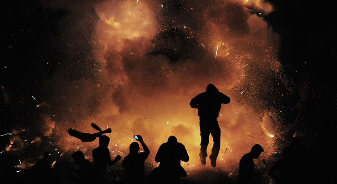 the photograph. They are looking towards the background, in which a large, orange firework is exploding.