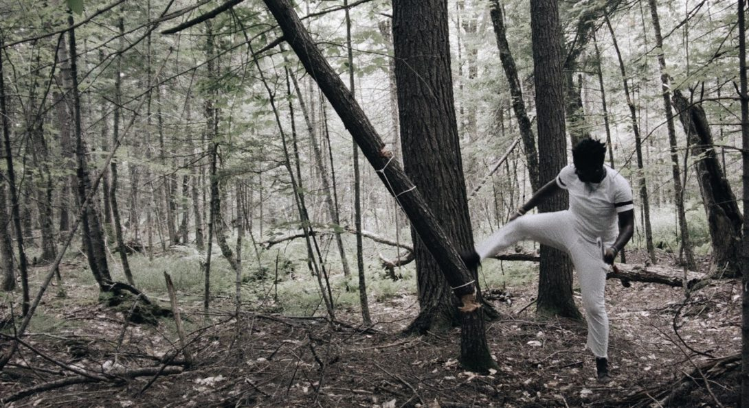 A photograph of a middle aged person in a woods setting. They are wearing all white, and are kicking a tree down.