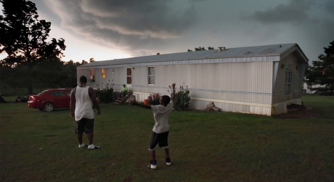 A photograph of a middle-aged person and a younger-aged person are standing in a yard of a mobile home, at dusk.