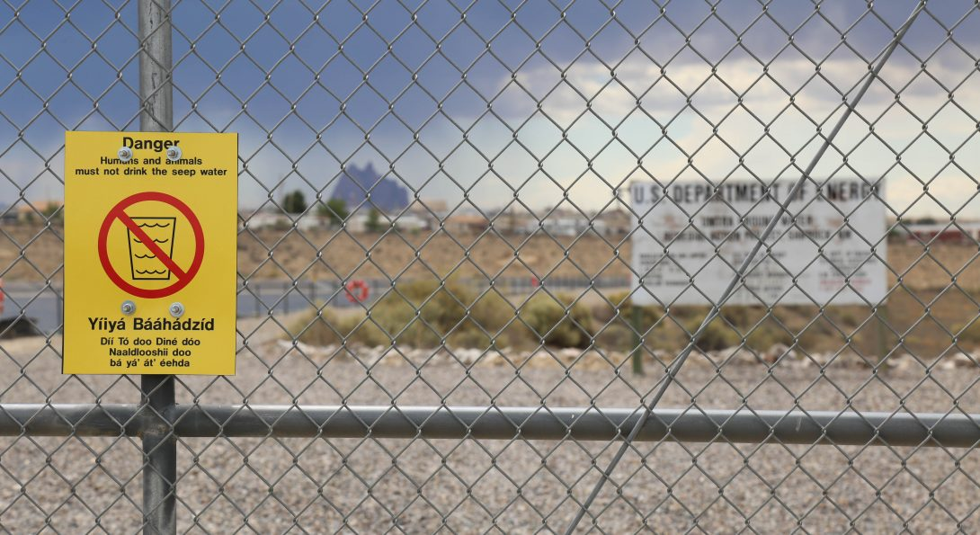 """A photograph of a metal fence stands in front of a flat field. A small area of water is situated on the left side. Behind the fence, a large white billboard reads """"U.S Department of Energy"""". Posted on the fence, a yellow sign with a red circle cross out symbols warns """"Danger, humans and animals must not drink water."""""""