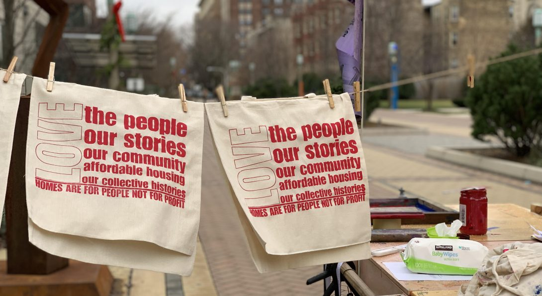 """A photograph of two beige textiles with bold, red text printed over top. The textiles are displaced on a clothing pin string in an outside area. The red bold text writes, """"LOVE the people, our stories, our community, affordable housing, our collective histories. Homes are for people, not for profit"""""""