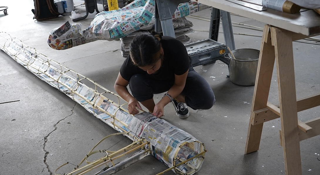 A photograph of a middle-aged person crouched onto the ground. They are working on long, circular sculpture with materials of wood and newspaper
