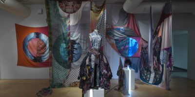 A dress form stands in the middle of a room filled with textiles hung from the ceiling. On the form is a denim outfit with a billowing skirt made of flannel scraps.