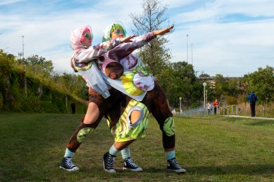 Two people sharing one costume stand in alignment with one arm up diagonally.