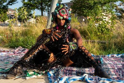 A dark skinned person in an elaborate costume sits in a natural area with their legs spread.