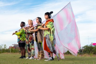 Four young people stand in a line, each are carrying a white and pink flag over their shoulder.