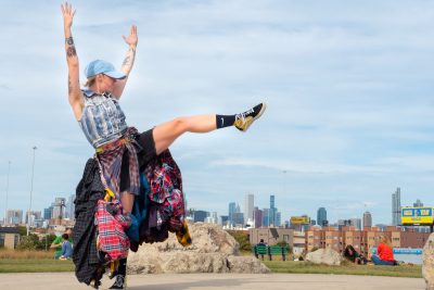 A light-skinned person in a baseball cap and skirt made of many layers of flannel, raises her leg, mid-dance.