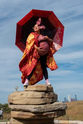 A person dressed in red with a red umbrella stands at the top of a rock.