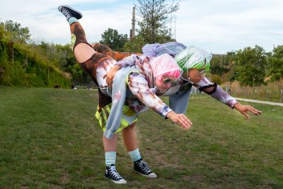 Two people with one leg each in a single pant leg both lift their other leg high into the air behind them.
