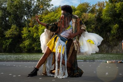 A dark-skinned person wearing a fringed costume and with many paper bags attached to the arms is caught mid-dance.