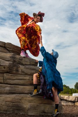 One person in an orange costume stands at the top of a rock. They reach down towards a person in blue, grasping their hand.