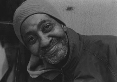 A black and white photograph, of a close-up shot of a beard, likely-black, man tilting his head to the left of the image in a beanie hat and a coat giving a closed-lipped warmth filled smile, facing towards the viewer.